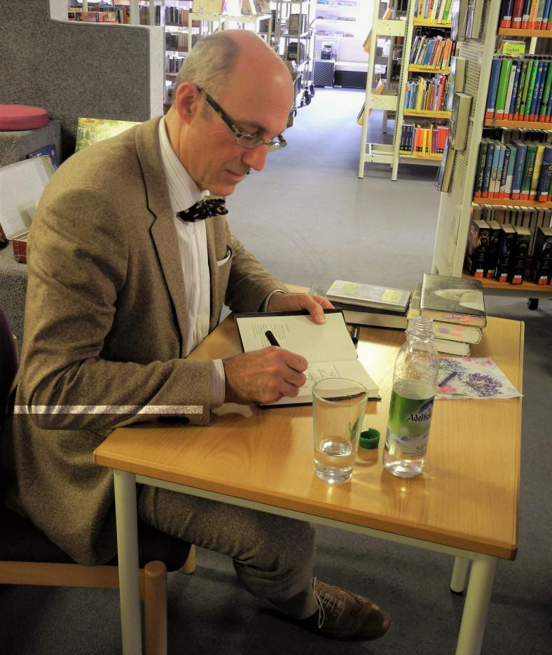 Der Autor beim Signieren, der Büchertisch war schnell ausverkauft